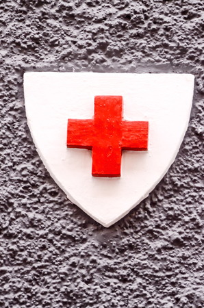 helvetica: Red Cross Medical Sign Over a White Background