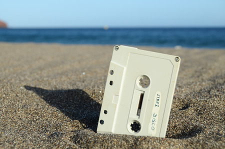 cassette tape: Ancient Retro Musicassette on the Sand near the Water