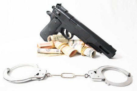 Financial Crime Concept Gun and Money on a White Background photo