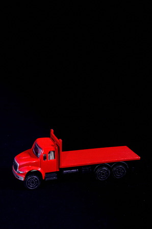 comics car: Red Toy Figurine Truck on a Black Background