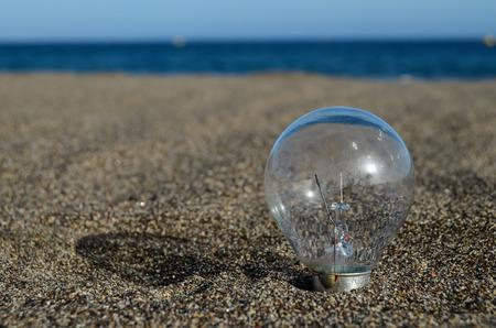 burnt out: Light bulb on the beach Idea Concept