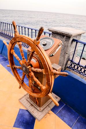 shroud: Old Vintage Wooden Helm Wheel near Blue Ovcean Stock Photo