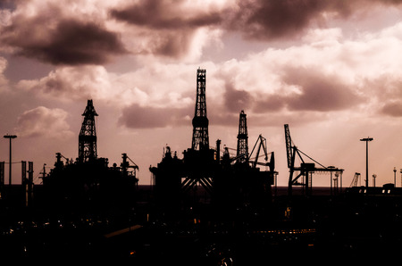 Oil Drilling Rig Silhouette over a Cloudy Sky photo
