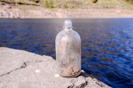 gass: Old Dirty Vintage Gass Bottle near the Water