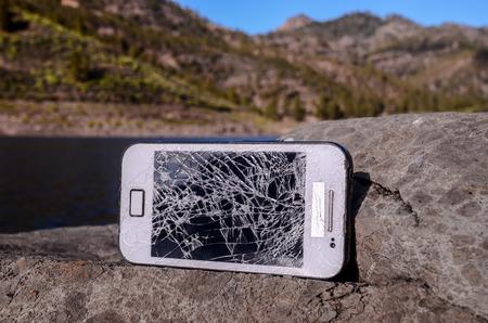 Broken Modern White Smartphone on the Floor photo