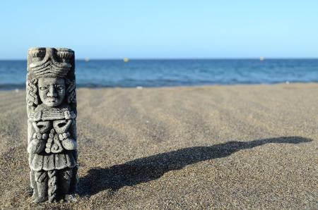 Ancient Maya Statue on the Sand Beach near the Ocean Stock Photo