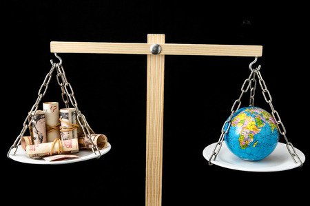 Globe Planet Earth en geld op een Two Pan Balance Stockfoto