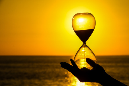 Time Concept Hourglass and Sun Setting on the Atlantic Ocean photo