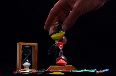Deadline Concept Broken Hourglass with Yellow Sand on Black Background photo