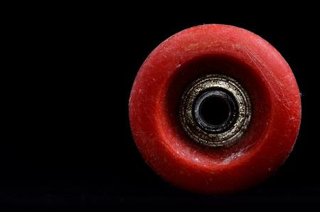 Old Vintage Consumed Skate Wheel on a Black Background photo