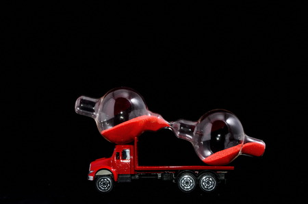 Time Transportation Concept Hourglass Watch on a Red Toy Truck over Black Background photo