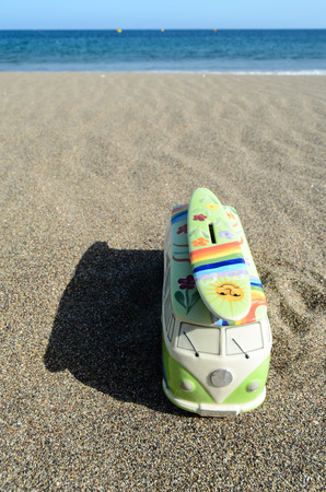surfboard fin: Detail of a Vintage Hippie Van Toy in the Beach with Surfboard on Roof