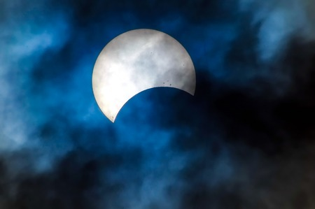 solar eclipse: Partial Solar Eclipse on a Cloudy Day  Stock Photo