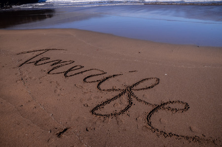 Word Written on the Sand of a Tropical beach photo