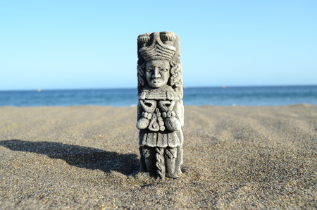 Ancient Maya Statue on the Sand Beach near the Ocean photo