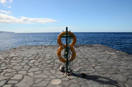 lifesaving: Yellow Life Saver on a Pier in Canary Islands el Hierro Spain Stock Photo