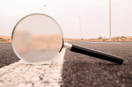 Travel Concept Magnify Glass Loupe on the Asphlat Road Stock Photo