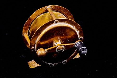 One Vintage Old Metal Fishing Reel on a Black Background photo