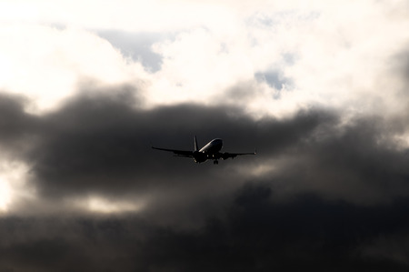 airplane landing: Silhouette of an Airplane Landing over a evening sky
