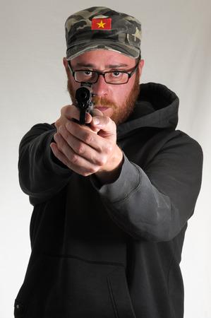 male killer: Black Dressed Young Man Holding a Pistol Gun