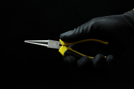 black grip: Pliers and a Hand on a Black Background