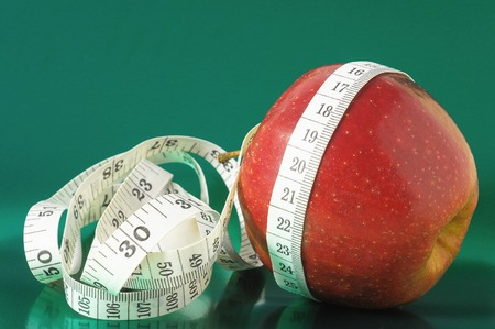 Measuring Tape Wrapped Around a Red Apple as a Symbol of Diet photo