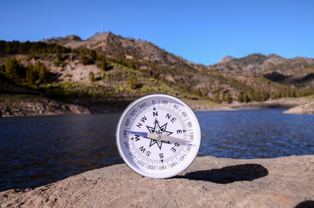 orientation: Orientation Concept - Analogic Compass Abandoned on the Rocks Stock Photo