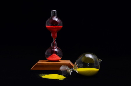 Deadline Concept Broken Hourglass with Yellow Sand on Black Background