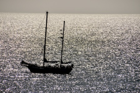 Backlight Picture of a Silhouette Boat in the Ocean photo