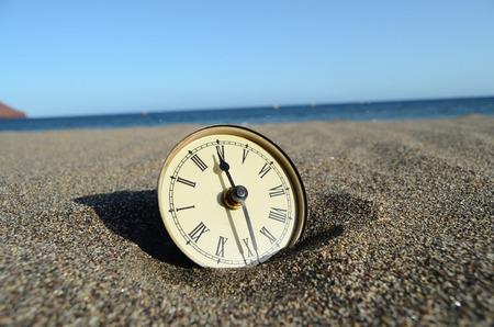 Classic Analog Clock In The Sand On The Beach Near The Ocean photo