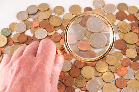 Picture of a Business Money Concept Idea Coins and Loupe Magnify Glass photo