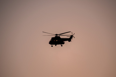 military helicopter: Military Helicopter Silhouette Flying over a Dark Sky Stock Photo