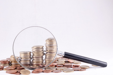 magnify glass: Picture of a Business Money Concept Idea Coins and Loupe Magnify Glass