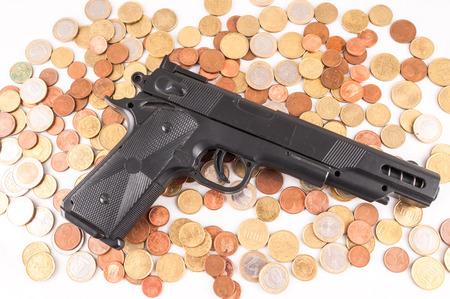 money concept: Picture of a Business Money Concept Idea Coins and Gun Stock Photo