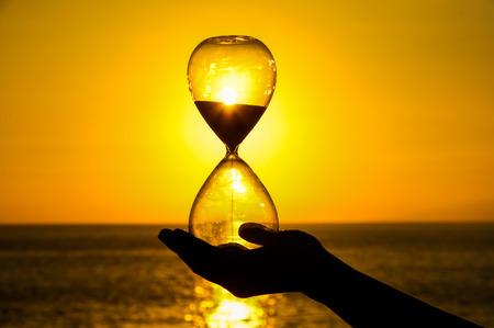 Tijd Concept Zandloper en Zon die op de Atlantische Oceaan