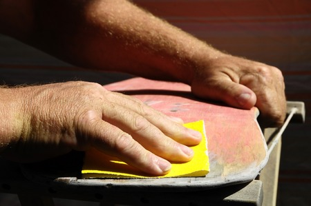 Restore an Old Skateboard with a Yellow Sandpaper Stock Photo