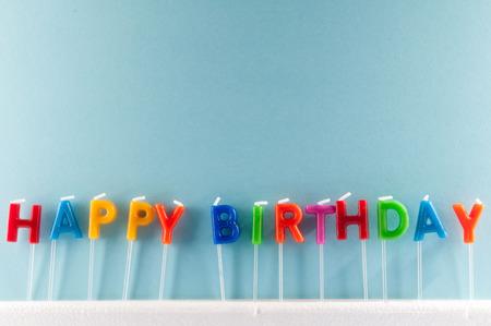 Veel gekleurde kaarsen met tekst Gelukkige Verjaardag