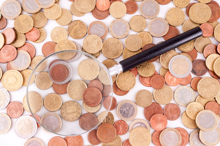 money concept: Picture of a Business Money Concept Idea Coins and Loupe Magnify Glass