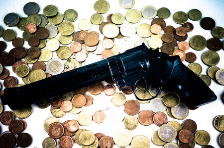 Picture of a Business Money Concept Idea Coins and Gun photo
