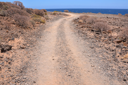 disappears: Long Straight Dirt Desert Road disappears into the Horizon. Stock Photo