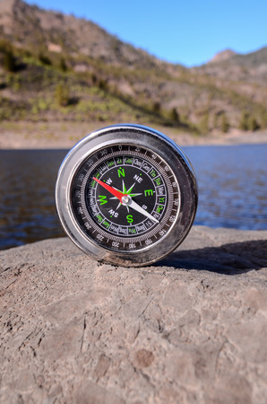 Orientation Concept - Analogic Compass Abandoned on the Rocks photo