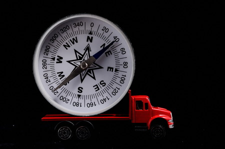 orientation: Orientation Transportation Concept Compass on a Red Toy Truck over Black Background
