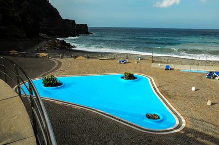 vallehermoso: Blue Swimming Pool near the Atlantic Ocean Stock Photo