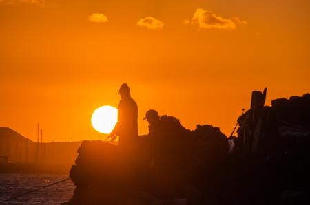 orange sunset: Fisherman Fishing Rod Silhouette at Orange Sunset