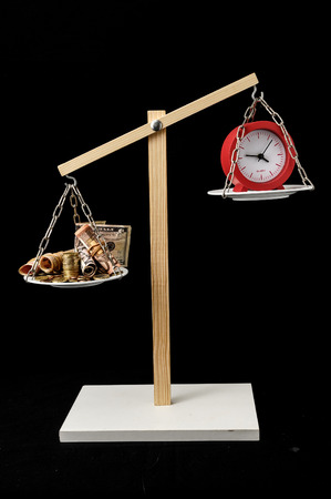 money concept: Time is Money Concept Clock and Currency on a Two Pan Balance