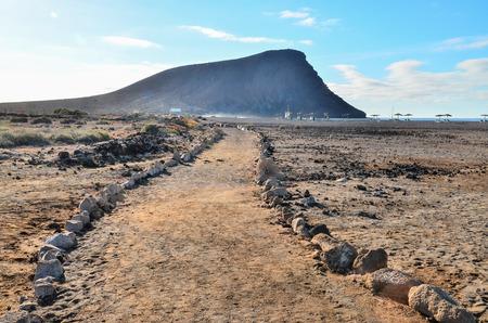 desert road: Long Straight Dirt Desert Road disappears into the Horizon. Stock Photo