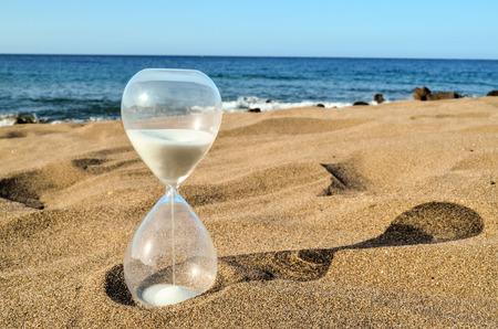 砂のビーチの砂時計の時計の写真画像