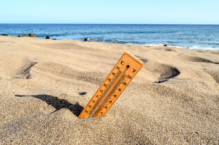 global warming: Photo Picture of a Thermometer on the Sand Beach