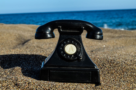 turistic: Photo Picture of an Old Phone on the Sand Beach