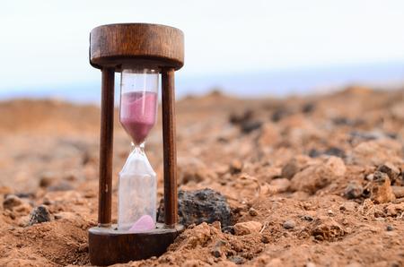 reloj de arena: Concepto de tiempo de reloj de arena en el desierto de roca Foto de archivo
